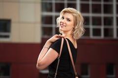 Glückliche junge blonde Frau im schwarzen Kleid Stockfotografie