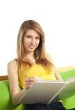Glückliche junge blonde Frau mit Buch Stockfotografie