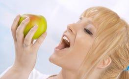 Glückliche junge blonde Frau mit einem Apfel Lizenzfreies Stockfoto