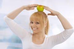 Glückliche junge blonde Frau mit einem Apfel Stockfoto