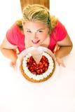 Glückliche junge blonde Frau mit Erdbeercremekuchen Stockfotos