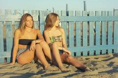 Glückliche junge blonde Frauen, die auf dem Strand sich entspannt bei Sonnenuntergang sitzen lizenzfreies stockbild
