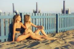 Glückliche junge blonde Frauen, die auf dem Strand sich entspannt am breiten Schuss des Sonnenuntergangs sitzen stockbild