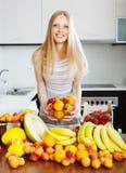 Glückliche junge blonde Hausfrau mit reifen Früchten Stockfotografie