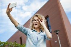 Glückliche junge blonde kaukasische Frau, die ein selfie Porträt mit Handy am modernen Backsteinmauergebäudehintergrund nimmt Stockfotos