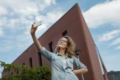 Glückliche junge blonde kaukasische Frau, die ein selfie Porträt mit Handy am modernen Backsteinmauergebäudehintergrund nimmt Lizenzfreie Stockbilder