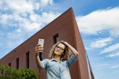 Glückliche junge blonde kaukasische Frau, die ein selfie Porträt mit Handy am modernen Backsteinmauergebäudehintergrund nimmt Lizenzfreies Stockfoto