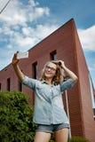 Glückliche junge blonde kaukasische Frau, die ein selfie Porträt mit Handy am modernen Backsteinmauergebäudehintergrund nimmt Stockfotografie