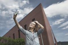 Glückliche junge blonde kaukasische Frau, die ein selfie Porträt nimmt Stockfoto