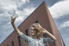 Glückliche junge blonde kaukasische Frau, die ein selfie Porträt nimmt Stockfotografie