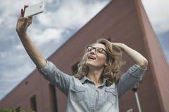 Glückliche junge blonde kaukasische Frau, die ein selfie Porträt nimmt Lizenzfreie Stockbilder