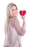 Glückliche junge blonde kaukasische Frau, die rotes Herz hält. Lizenzfreies Stockfoto