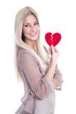 Glückliche junge blonde kaukasische Frau, die rotes Herz - lokalisiertes O hält Lizenzfreies Stockbild