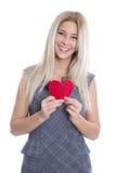 Glückliche junge blonde kaukasische Frau, die rotes Herz - lokalisiertes O hält Lizenzfreie Stockbilder