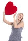 Glückliche junge blonde kaukasische Frau, die rotes Herz und Bums hochhält Lizenzfreies Stockbild