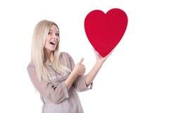 Glückliche junge blonde kaukasische Frau, die rotes Herz und Bums hochhält Lizenzfreie Stockfotos