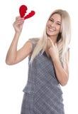 Glückliche junge blonde kaukasische Frau, die rotes Herz und das Zeigen hält Lizenzfreies Stockbild
