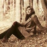Glückliche junge blonde Modefrau, die auf dem Boden im Herbstwald sitzt Lizenzfreie Stockfotos