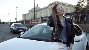 Glückliche junge Blondine, die auf dem weißen Auto sitzen stock footage