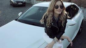 Glückliche junge Blondine, die auf dem weißen Auto sitzen stock video footage
