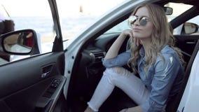 Glückliche junge Blondine, die im weißen Auto sitzen stock footage
