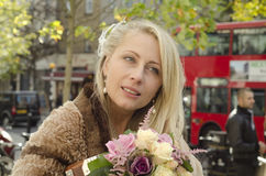Glückliche junge Braut mit Blumenstrauß Stockfotografie