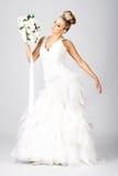 Glückliche junge Braut mit Blumenstrauß auf Weiß Stockfotografie