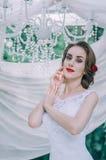 Glückliche junge Braut mit einer roten Rose in ihrem Haar, im Freien Lizenzfreie Stockfotografie