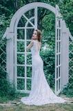 Glückliche junge Braut mit einer roten Rose in ihrem Haar steht nahe einem Whit Stockfotografie