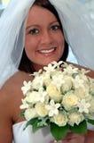 Glückliche junge Braut mit rosafarbenem Blumenstrauß stockfoto