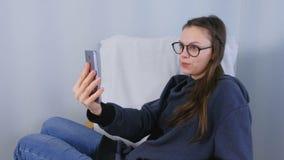 Glückliche junge brunette Frau in den Gläsern sprechen ein Videoschwätzchen an einem Handy, der im Lehnsessel sitzt stock video footage