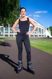 Glückliche junge Brunettefrau auf Rollschuhen im Park lizenzfreies stockbild