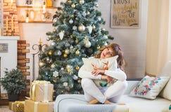 Glückliche junge Dame mit dem gelockten Haar sitzt nahe dem Weihnachtsbaum stockbild