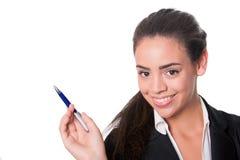 Glückliche junge Dame am Schreibtisch zeigend mit Stift Stockbild