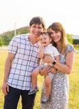 Glückliche junge Eltern mit kleinem Kind auf dem Feld lizenzfreie stockfotos