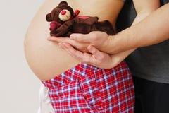 Glückliche junge Eltern zeigen Spielzeug ihres zukünftigen Babys Stockfotos