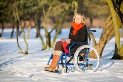 Glückliche junge erwachsene Frau auf Rollstuhl Stockbild