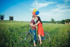 Glückliche junge erwachsene Paare in der Liebe auf dem Feld Zwei, Mann und Frau lächelnd und nach Fahrradreiten stillstehend Lizenzfreie Stockfotos