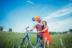 Glückliche junge erwachsene Paare in der Liebe auf dem Feld Zwei, Mann und Frau lächelnd und nach Fahrradreiten stillstehend Lizenzfreie Stockfotografie