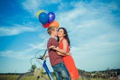Glückliche junge erwachsene Paare in der Liebe auf dem Feld Zwei, Mann und Frau lächelnd und nach Fahrradreiten stillstehend Lizenzfreie Stockbilder