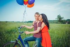 Glückliche junge erwachsene Paare in der Liebe auf dem Feld Zwei, Mann und Frau lächelnd und nach Fahrradreiten stillstehend Stockfotografie