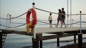 Glückliche junge Familie auf dem Pier durch das Meer stock footage