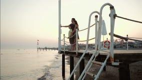 Glückliche junge Familie auf dem Pier durch das Meer stock video