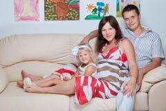 Glückliche junge Familie auf Sofa im Haus stockbild
