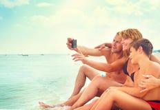 Glückliche junge Familie, die auf dem Strand sitzt und selfie nimmt stockfotografie