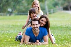 Glückliche junge Familie, die auf Gras liegt Stockfotografie