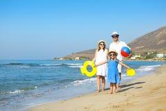 Glückliche junge Familie, die den Spaß läuft auf Strand bei Sonnenuntergang hat familie Stockfotos