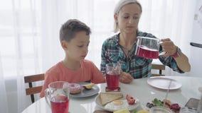 Glückliche junge Familie, die in der Küche frühstückt Nahrhafte Mahlzeit stock video