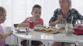 Glückliche junge Familie, die in der Küche frühstückt Nahrhafte Mahlzeit stock video footage