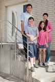 Glückliche junge Familie, die an der Türstufe steht Stockbild